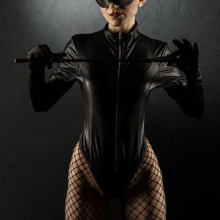 Spiele für Erwachsene. Schöne dominante brünette Vamp-Herrin in Latex-Körper, Handschuhe posiert mit Reitgerte. - Bild