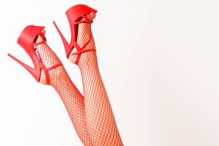 Sexy female legs in high heel red striptease shoes and fishnet stockings. - image
