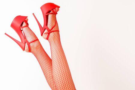 Sexy piernas femeninas en zapatos de striptease rojos de tacón alto y medias de red. - imagen Foto de archivo