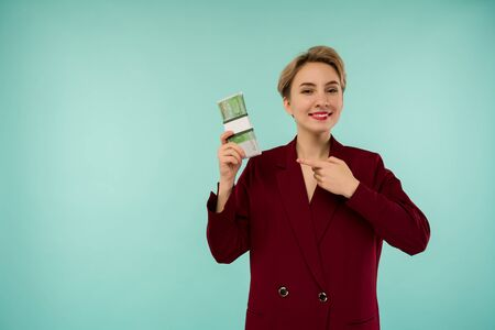 Young businesswoman smiling hold towards a stack of money and pointing finger to cash isolated on blue background - Image