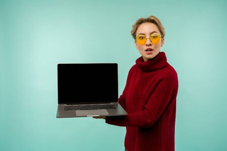 Surprised happy brunette woman in sweater showing blank laptop computer screen while looking at the camera with open mouth over blue background - image