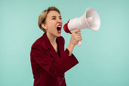 Angry businesswoman candidate with a megaphone on blue background - Image Zdjęcie Seryjne