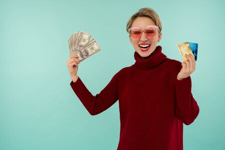 Portrait of happy young woman holding credit card and money in hand smiling and looking at camera on isolated blue background feeling positive and enjoy - image