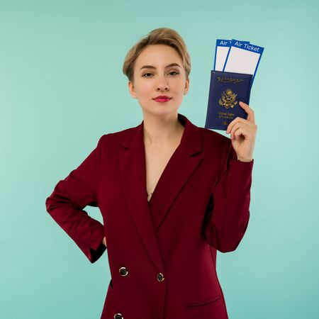 Its time to travel. A modern trendy smiling woman in red suit with air tickets and a passport in her hand.