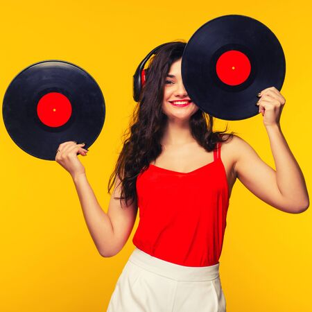 Young woman in headphones looking at camera and closing her face with vinyl record. - toned Image