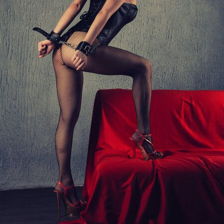 Beautiful sexy lady in bdsm outfit. Close up of model with hand in bondage near red sofa - toned image Zdjęcie Seryjne