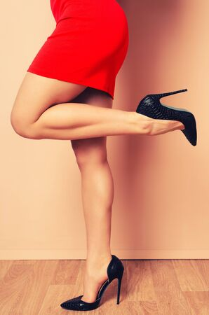 Female Legs with black high-heeled shoes on a pink wall background - Image toned