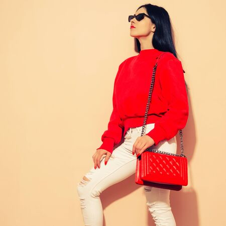 Fashion young woman in white jeans and sweater with red bag clutch in hands near wall toned image