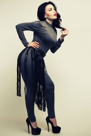 BDSM outfit fringe skirt on a woman in a gray fitted spandex jumpsuit. Fetish concept. - Image toned 免版税图像
