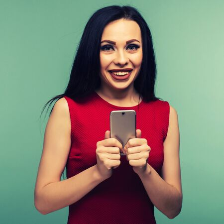 Excited laughing woman in red dress standing and using mobile phone over blue background - Image toned