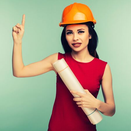 Young female engineer in orange helmet with drawings points finger up isolated on blue background - Image toned