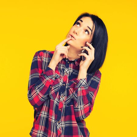 Young woman looking surprised, talking on mobile phone, conducting pleasant conversation isolated on yellow background. toned