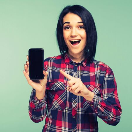 Surprised happy brunette woman in plaid shirt showing blank smartphone screen and pointing on it while looking at the camera with open mouth over teal background - Image toned