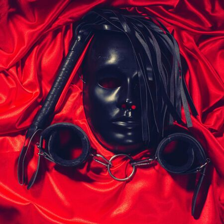 Bondage, kinky adult sex games, kink and BDSM lifestyle concept with a mask, pair of leather handcuffs, flogger, ball gag and a coller with a leash attached on red silk toned Stock Photo