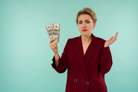A young businesswoman bankrupt holds in her hands the remaining money. Depressed state on the day of loan payment. On blue background with copyspase Zdjęcie Seryjne
