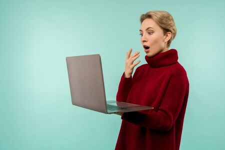Surprised happy blonde woman in sweater looking laptop computer screen with open mouth over blue background - image Zdjęcie Seryjne