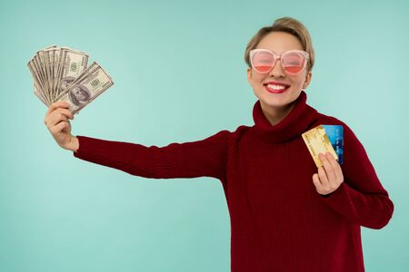 Portrait of happy young woman in pink sunglasses holding credit card and money in hand smiling and looking at camera on isolated blue background feeling positive and enjoy - image