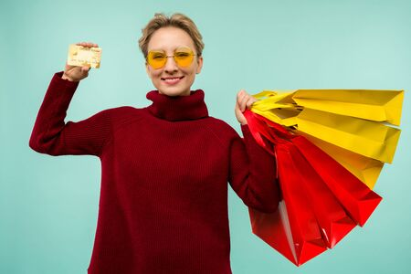 Image of a beautiful happy young blonde woman posing isolated over blue wall background holding shopping bags and credit card. Black Friday Holiday Concept. Sale Zdjęcie Seryjne