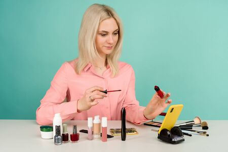 Candid shot of cute young Caucasian woman blogger presenting beauty products and broadcasting live video to social network, using lip gloss while recording everyday make up tutorial Zdjęcie Seryjne