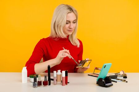 Candid shot of cute young Caucasian woman blogger presenting beauty products and broadcasting live video to social network, using brush to apply eyeshadow while recording everyday make up tutorial Zdjęcie Seryjne