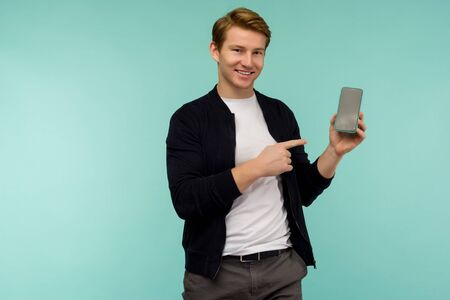 Cheerful sporty red-haired guy shows a finger on the smartphone screen on a blue background. - image Zdjęcie Seryjne