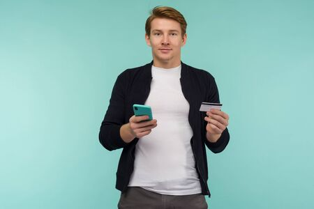 Cheerful sports red-haired guy conducts online payment and looks at the smartphone screen on a blue background. - image Zdjęcie Seryjne