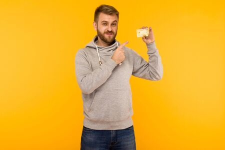 Attractive man in a gray hoodie points a finger at the credit card that is holding in his hand on a yellow background - image