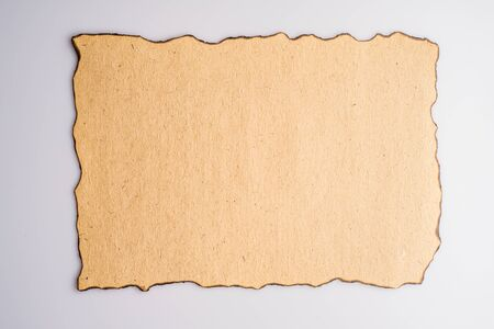 Aged and stained paper with fire damaged and burned edges on white background