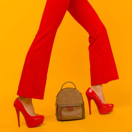 Woman fashion with beautiful small backpack handbag with red high heels shoes on yellow background - image
