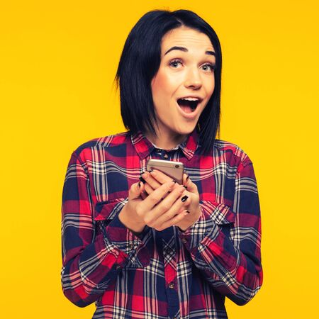 Excited laughing woman in plaid shirt standing and using mobile phone over yellow background - Image toned