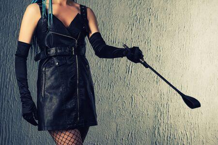 Dominante Frau in einem Lederkleid mit einem Stapel in der Hand. - Bild getönt
