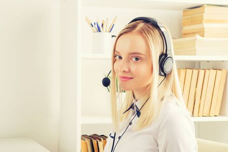 Portrait of happy smiling female customer support phone operator at workplace. - Image toned Zdjęcie Seryjne