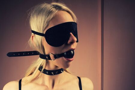 lady in outfit. Close-up girl in mask and collar with gag in mouth -Image toned