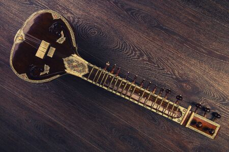Indian musical instrument sitar lying on the wooden floor- image Toned