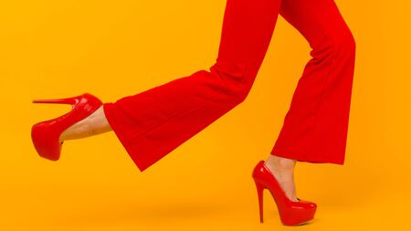 The business woman running somewhere hurrying up isolated on yelow background. Stylish red heels and pants on thin female legs
