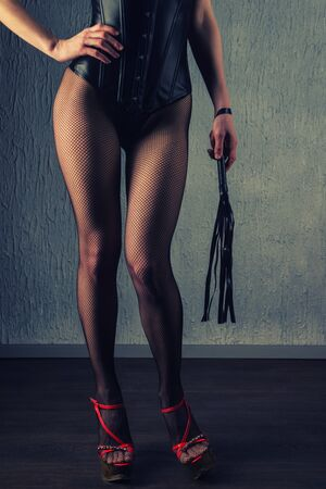 Sexy lady in bdsm outfit. Beauty woman with whip in leather corset.- image Toned