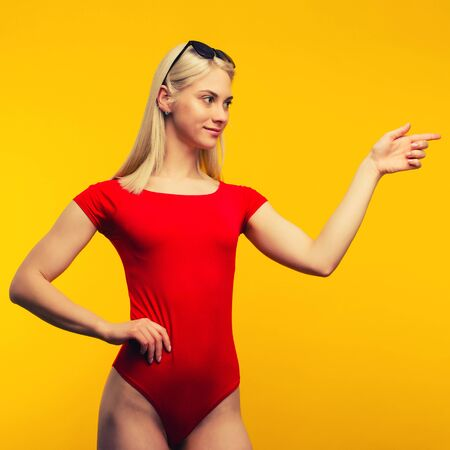 pretty blond lifeguard in red swimsuit and sunglasses points finger on yellow background. Stock Photo