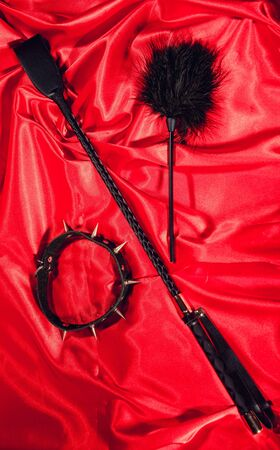 Bondage, kinky adult sex games, kink and BDSM lifestyle concept with a whip, feather stick, collar on red silk. toned