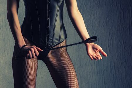 Sexy lady in bdsm outfit. Beauty dominant woman with spank in leather corset.- image Toned