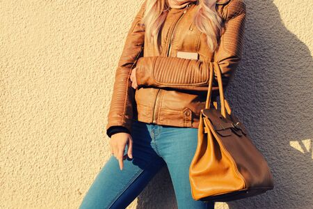 Young stylish woman in black trendy outfit with big bag in hand street look Stockfoto