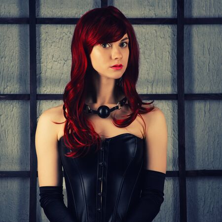 Portrait of Red-haired girl in a leather corset with gag ball. Bdsm outfit. toned Archivio Fotografico