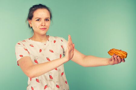 Portrait of pimply teen girl hows hands stop on a delicious cake on blue background. toned