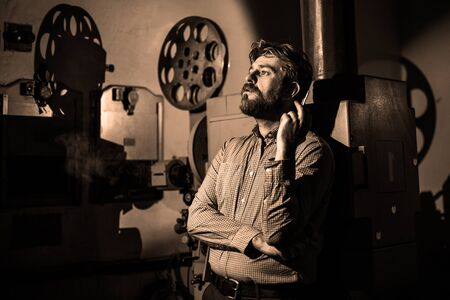 beautiful hipster man standing near a film projector in the room projectionist Stock Photo