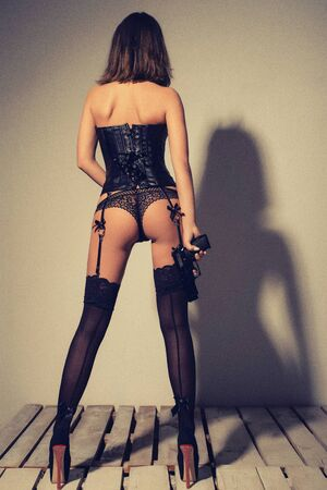 sexy young woman in a leather black corset, lacy panties and stockings stands with her back on a wooden floor and holds a gun in her hands Banco de Imagens