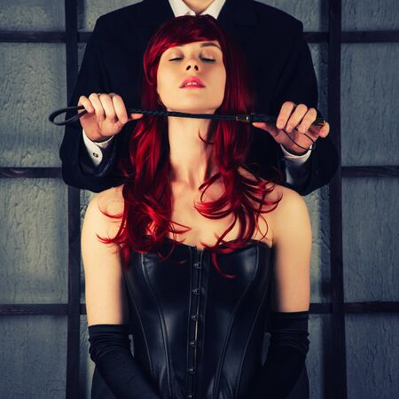 Adult games. A man holds a spank near the neck of a red-haired girl in a leather corset. Bdsm outfit. toned