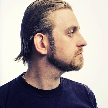 Portrait d'une jolie barbe blonde hipster de profil sur fond gris