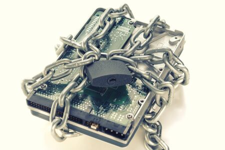 Metal chain and lock around hard disc drive on white. Secure data. Focusing on the center of the chain