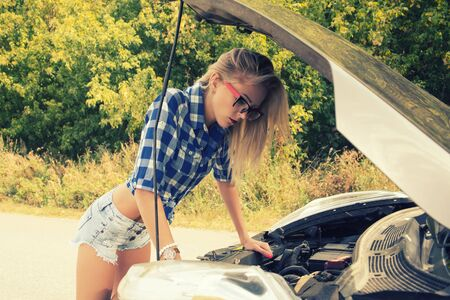 Beautiful slim girl in shirt and shorts looks in open car hood on a road