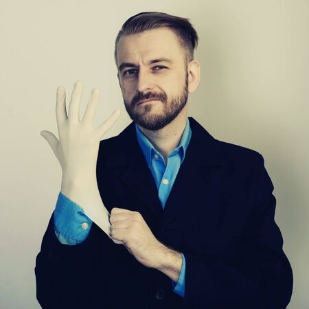 young stylish bearded businessman in suit and blue shirt puts on medical glove on gray background