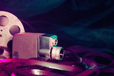 8 mm movie camera with a reel of film in green and purple smoke. dark background